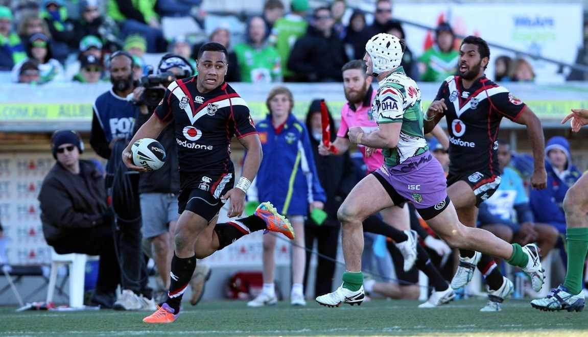 Ngani Laumape chased by Jarrod Croker.Raiders v Warriors. NRL rugby league match. GIO Stadium, Sydney Australia. Saturday 3 August 2014. Photo: Paul Seiser/Photosport.co.nz